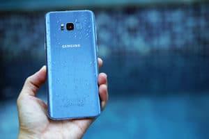Holding a blue Samsung Galaxy S8 in the rain. It's waterproof!