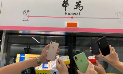 Apple fans posing in train station named after Huawei